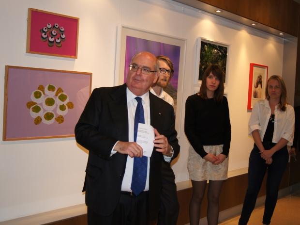 Botschafter Ritchie steht neben den Kuratoren der Austellung und der Stipendiatin des Künstlerhaus Bethanien vor den Bildern und begrüßt die Gäste. Insgesamt sind vier Leute auf dem Bld zu sehen.