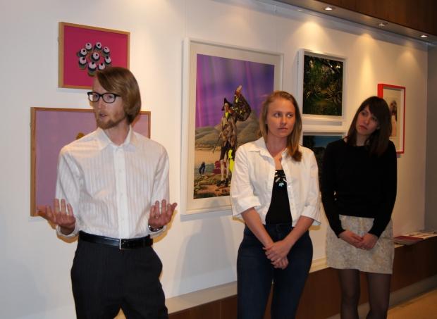 Michael Dooney von der Galerie Pavlova spricht über das Konzept der Ausstellung. Er steht vor den Bildern. Neben ihm stehen Elizabeth Willing und Natalie Bergschwinger
