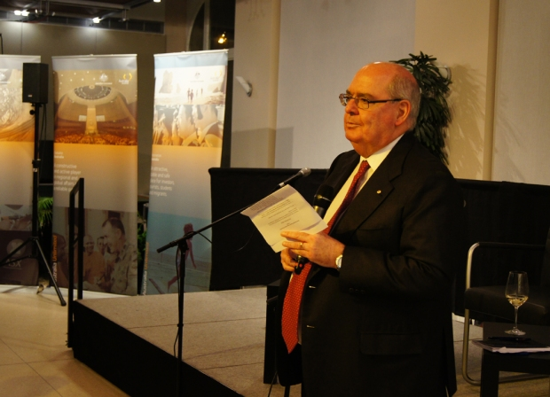 Ambassador Ritchie in front of the panel welcoming the guests