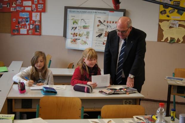 Botschafter Ritchie spricht mit zwei Kindern über verschieden Vogelarten. Die Mädchen sitzen am Tisch und der Botschafter steht daneben.