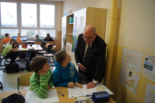 Botschafter Ritchie steht neben zwei Schülern, die am Tisch sitzen und spricht mit ihnen über Australien. Vor ihnen liegt eine Australienkarte auf dem Tisch.