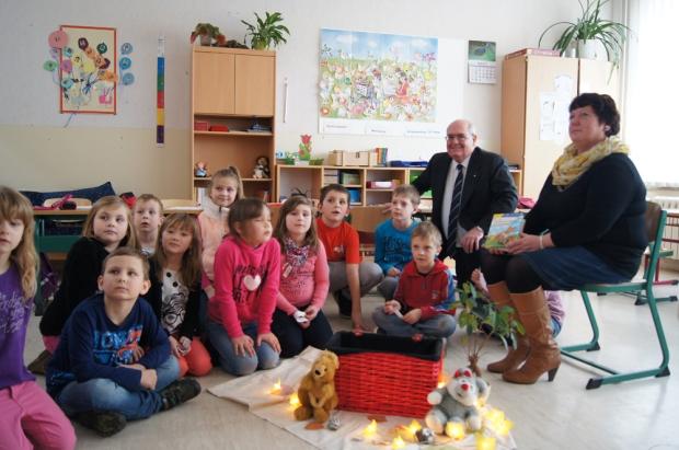 Der Botschafter sitzt zusammen mit einer Gruppe Schulkinder auf dem Boden. Daneben sitzt eine Lehrerin und zeigt ein australisches Buch. Die Kinder lernten australische Bücher kennen.