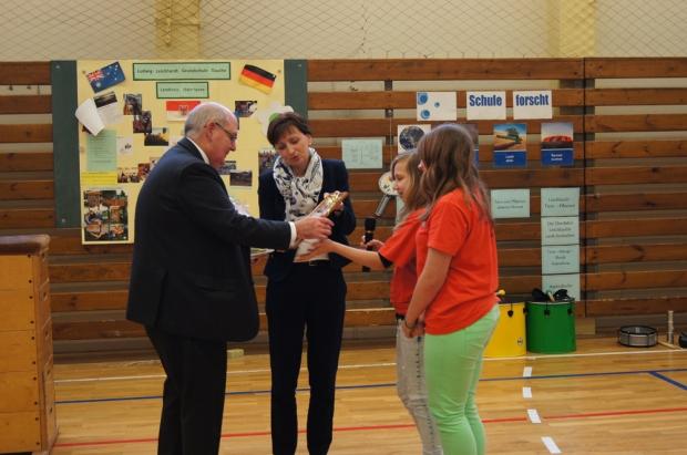 Die Schulleiterin und zwei Kinder übereichen dem Botschafter in der Turnhalle ein Geschenk. s ist selbst geimkerter Honig.