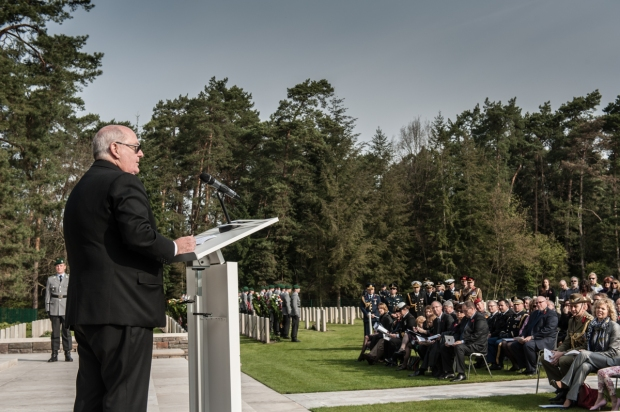 Ambassador Ritchie giving a speech at theCommonwealth War Graves Commission's First World War cemetery at Stahnsdorf. The Ambassador stands while guests are seated in fron of him an listining to him speaking.