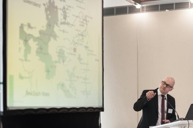 Dr. Stefan Klose vom Bundesministeriums für Umwelt, Naturschutz, Bau und Reaktorsicherheit steht am Rednerpult und hält einen Vortrag, hinter ihm ist eine Leinwand für den Powerpoint-Vortrag abgebildet