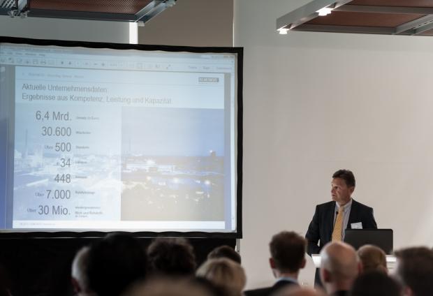 Torsten Weber, der Managing Director bei REMONDIS International hält einen Vortrag am Rednerpult. Hinter ihm steht eine Leinwand für seine Powerpoint-Präsentation.