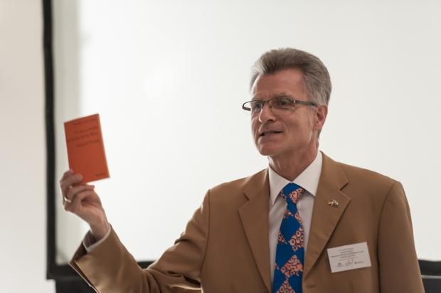 Dr. Rudolf Teuwsen vom Bundeskanzleramt. In der Hand hält er ein Reclam Heft, um zu zeigen, was er dort studiert hat - Philosophy (Thomas von Aquin).