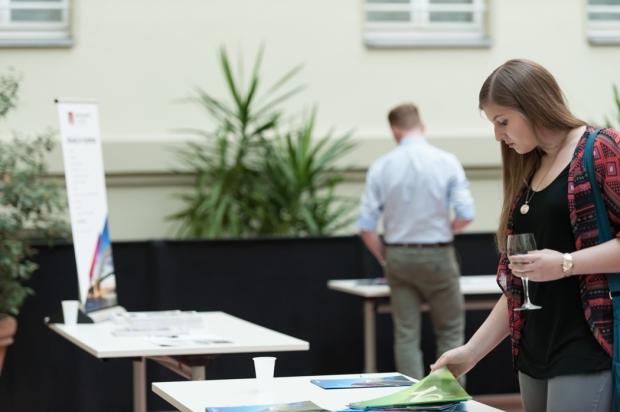 Mädchen schaut sich Informationsmaterial an. Das material ist auf Tischen im Innenhof der Australischen Botschaft ausgelegt.
