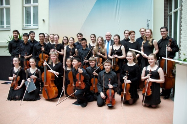 Group photo of the Melbourne String Ensemble in the Embassy courtyard showing the group with their instruments.