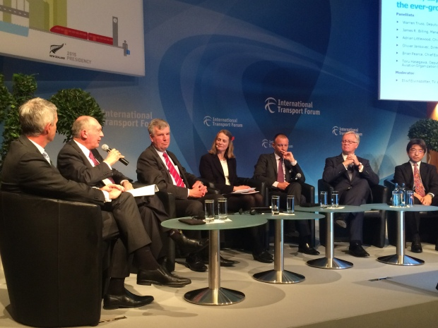 Different people sitting around a panel and talking at the International Transport Forum