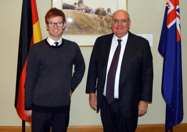 Our intern Mark together with Ambassador Ritchie in front of a German and Australian flag in the embassy building.