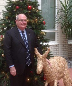 Botschafter Ritchie steht neben einem Strohkänguru vor einem Weihnachtsbaum