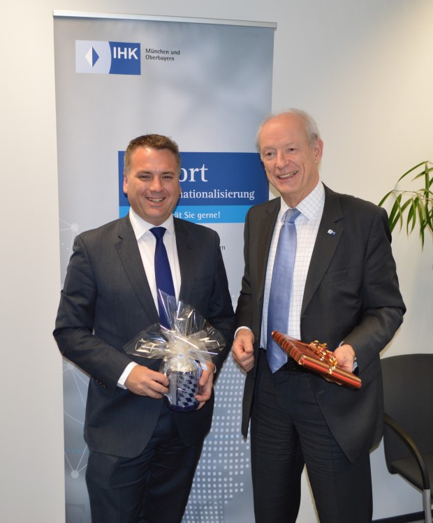 Minister Briggs stands next to Peter Driessen, Managing Director IHK Munich. They have exhanged gifts and hold them in their hands. Briggs has received a Bavarian cup and Driessen holds a wrapped package.