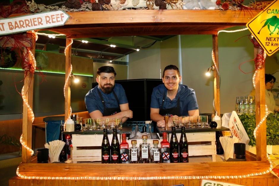 Do-It-Yourself Cocktail Stand, die zwei Barkeeper stehen dahinter und lachen in die Kamera.